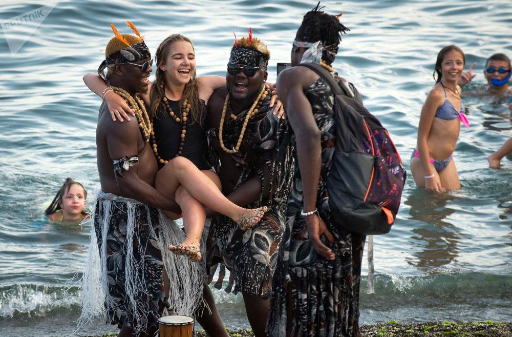 Menina tira fotos com estrangeiros em uma das praias da Crimeia