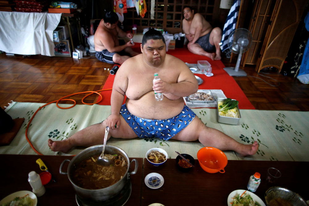 Lutador de sumô come sopa tradicional, Japão