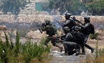 Confronto entre manifestantes palestinos e soldados israelenses na Cisjordânia.