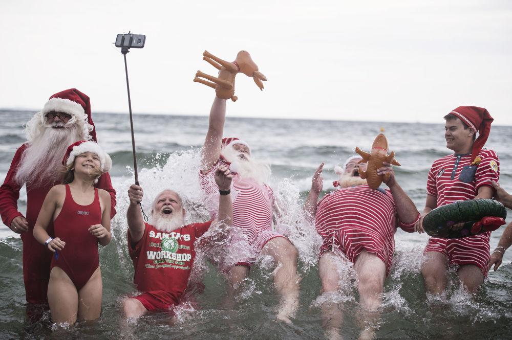 Papais Noéis se banham em um parque de diversão durante o Congresso Internacional de Papais Noéis, realizado anualmente em Copenhague