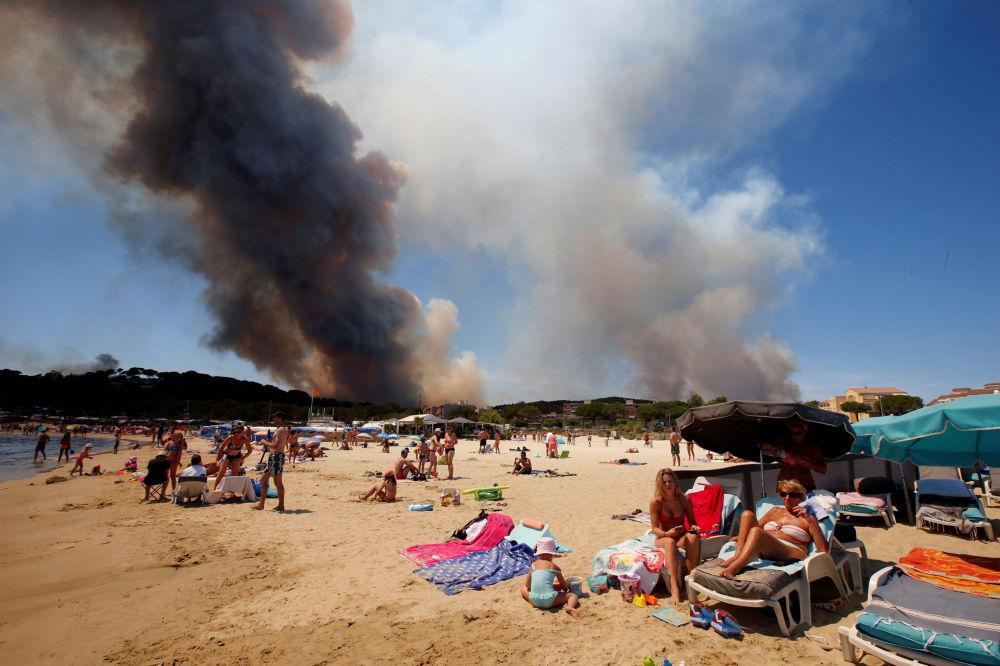 Fumaça produzida pelos incêndios florestais paira por cima das praias francesas enquanto os turistas desfrutam do sol no local Bormes-les-Mimosas