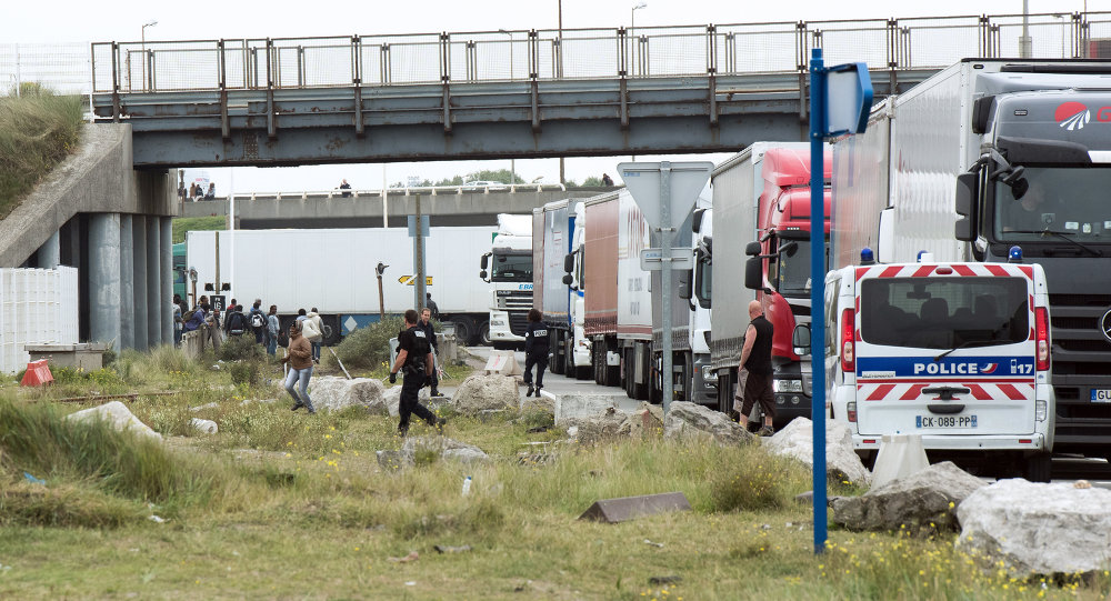 Policemen stand guard next to truck queuing to board a ferry to Great Britain to prevent migrants to reach the UK illegally.