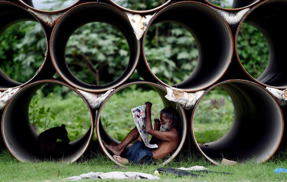 Indiano lê o jornal dentro de um tubo, na cidade de Nova Deli