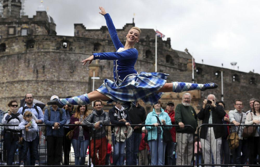 A dançarina Elayne Seaton, do clube Tattoo Dance Company, se apresenta junto ao Palácio de Edimburgo no âmbito da Parada Real de Orquestras Militares escocesa