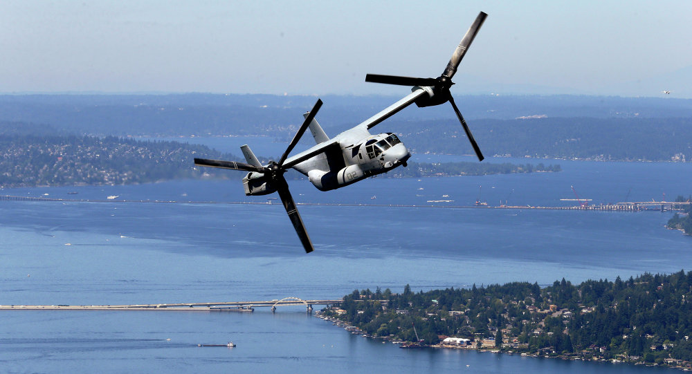 An MV-22B Osprey aircraft flies in view of Lake Washington.