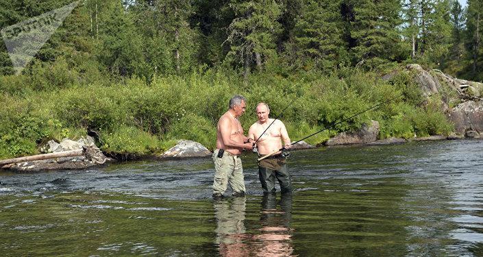 O presidente russo Vladimir Putin e o ministro da Defesa Sergei Shoigu pescam em um dos lagos de montanha na república de Tuva