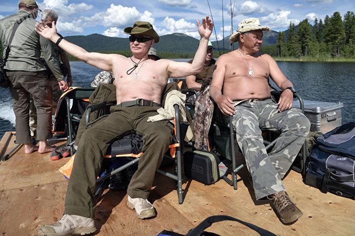 O presidente russo Vladimir Putin e o ministro da Defesa Sergei Shoigu tomam banhos de sol em um dos lagos de montanha na república de Tuva