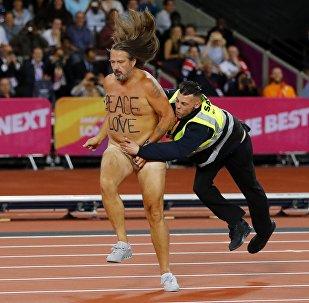 Um manifestante nu é abordado por um segurança depois de invadir a pista de corrida no mundial de atletismo em Londres.