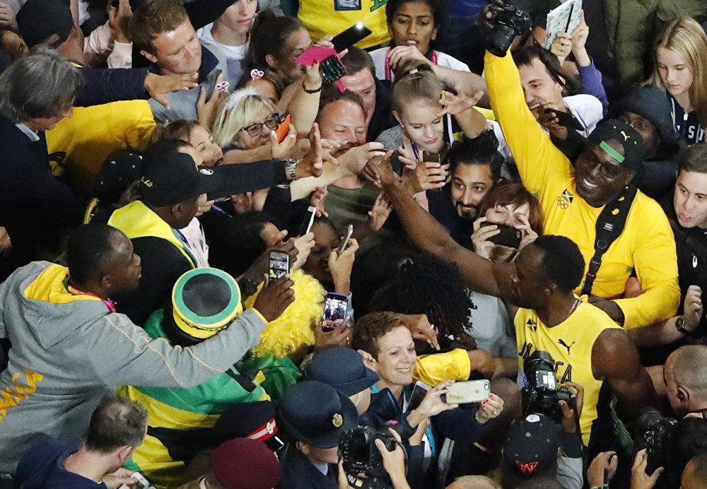 Usain Bolt é abraçado por torcedores após a corrida.