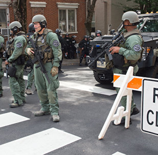 Agentes das forças especiais de Charlottesville bloqueiam rua da cidade durante confrontos entre manifestantes