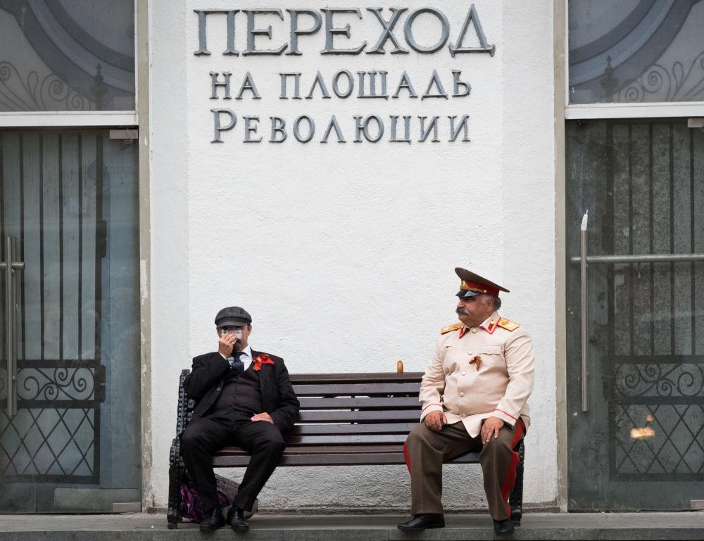 Atores vestidos de Lenin e Stalin sentados num banco no centro de Moscou