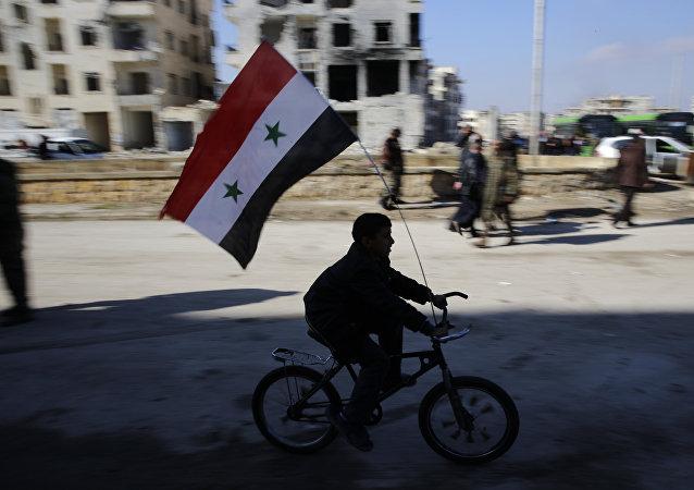 Um menino de bicicleta com uma bandeira da Síria (arquivo)