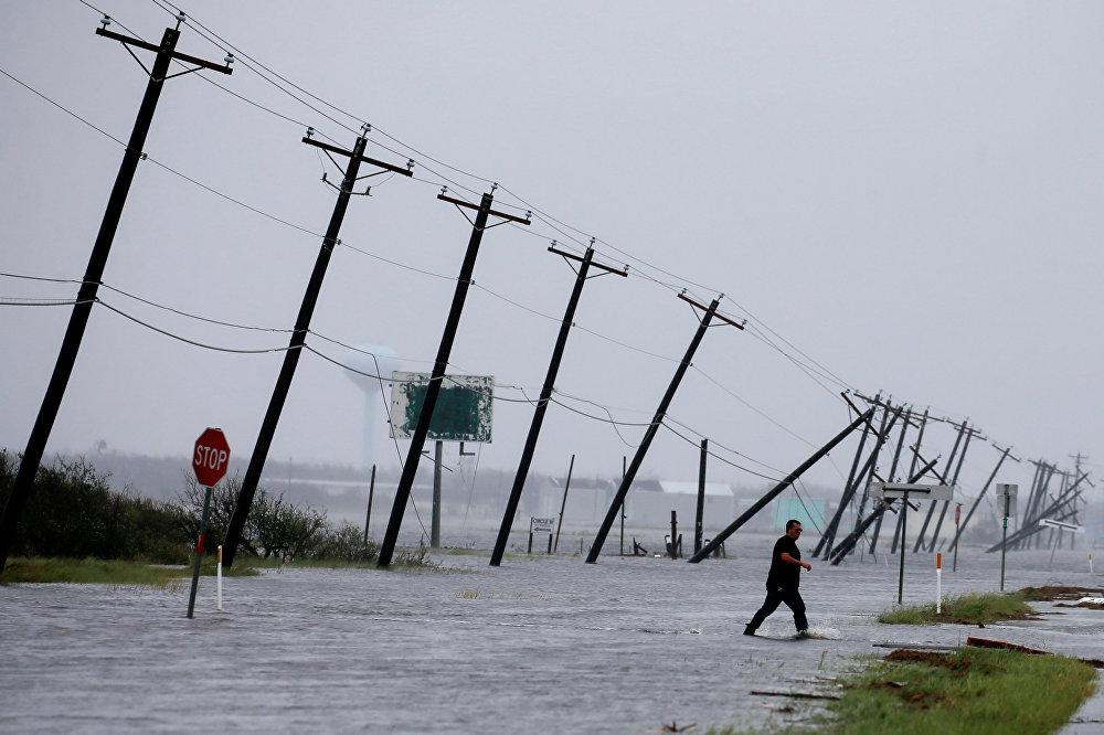 Homem caminha em meio a rodovia alagada em Rockport, Texas