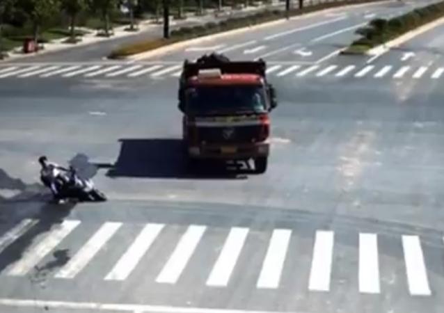 O homem caiu de sua motocicleta elétrica na estrada da província de Zhejiang (China). Por pouco não entrou nas rodas deste caminhão.