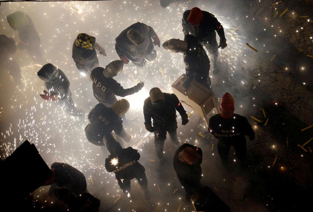 Pessoas lançam fogos de artifício durante o festival anual Corda no povoado de Paterna, Espanha