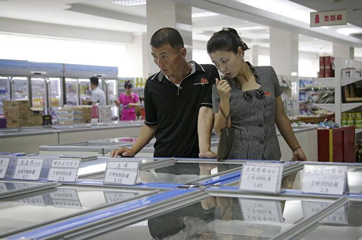 Compradores escolhendo produtos no supermercado Potonggang