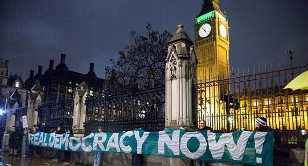 Ativistas do Occupy Democracy estendem faixa em frente ao Parlamento britânico