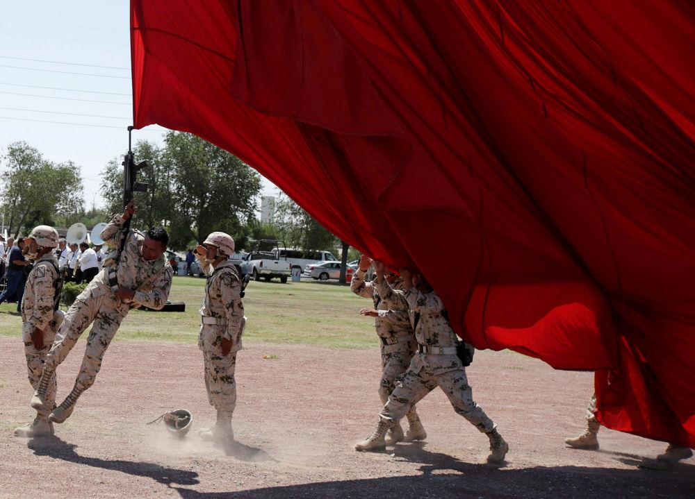 Soldado engancha inadvertidamente seu rifle na bandeira nacional, durante os preparativos para o 207º  aniversário da Independência do México da Espanha