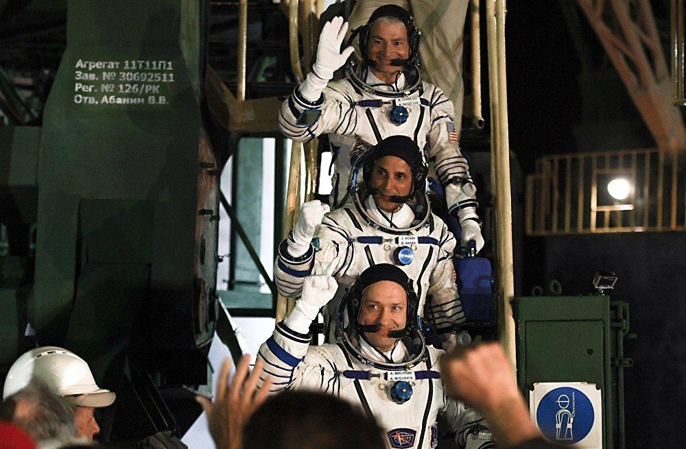 Os astronautas norte-americanos Mark Wandae Hai e Joseph Aqaba, e o cosmonauta russo Aleksandr Misurkin (de cima para baixo)