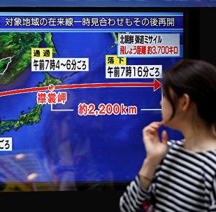 Uma pedestre em Tóquio olhando para transmissão de notícias sobre o lançamento do míssil, em 15 de setembro de 2017