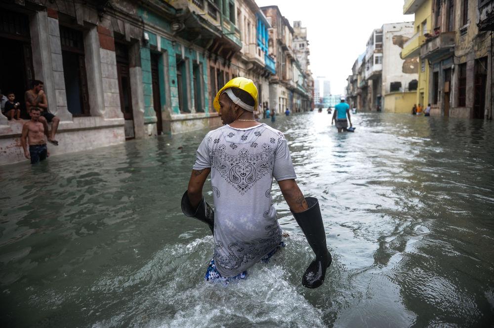 Cubanos andam pelas ruas inundadas de uma rua em Havana depois do furacão Irma ter atingido a capital