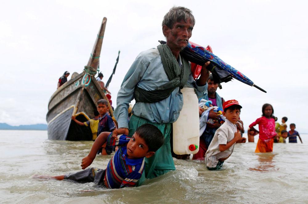 Um refugiado da comunidade rohingya puxa uma criança ao sair na costa bengali após atravessar a fronteira do Bangladesh