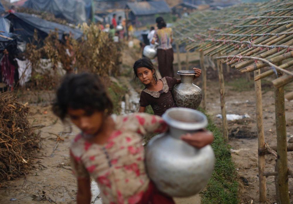 Menina refugiada rohingya carrega um jarro de metal com água em um campo de refugiados bengali