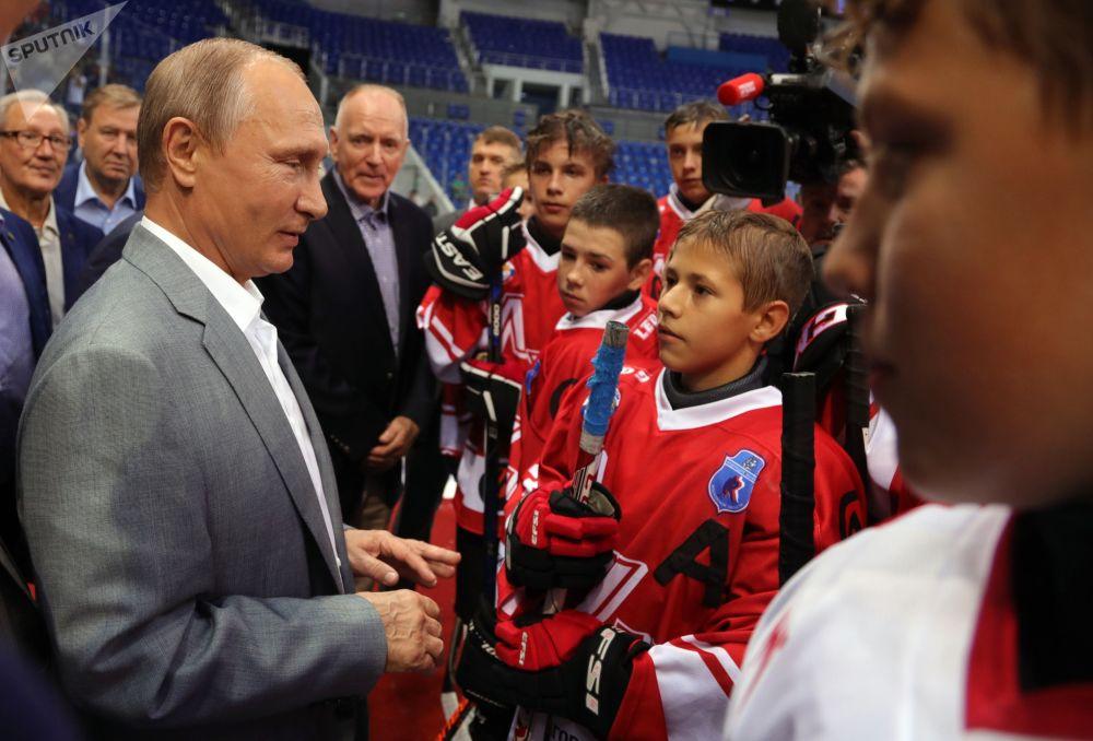 O presidente russo Vladimir Putin junto com jogadores de hóquei soviéticos e canadenses que tomaram parte da legendária supersérie de 1972 em Sochi se comunica com jovens atletas