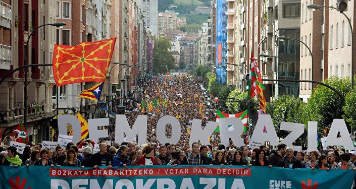 Milhares de manifestantes caminham atrás de uma bandeira em que se lê Votar para decidir Democracia, Catalunha, estamos com você, durante uma marcha organizada pela organização de independência pro-basca.