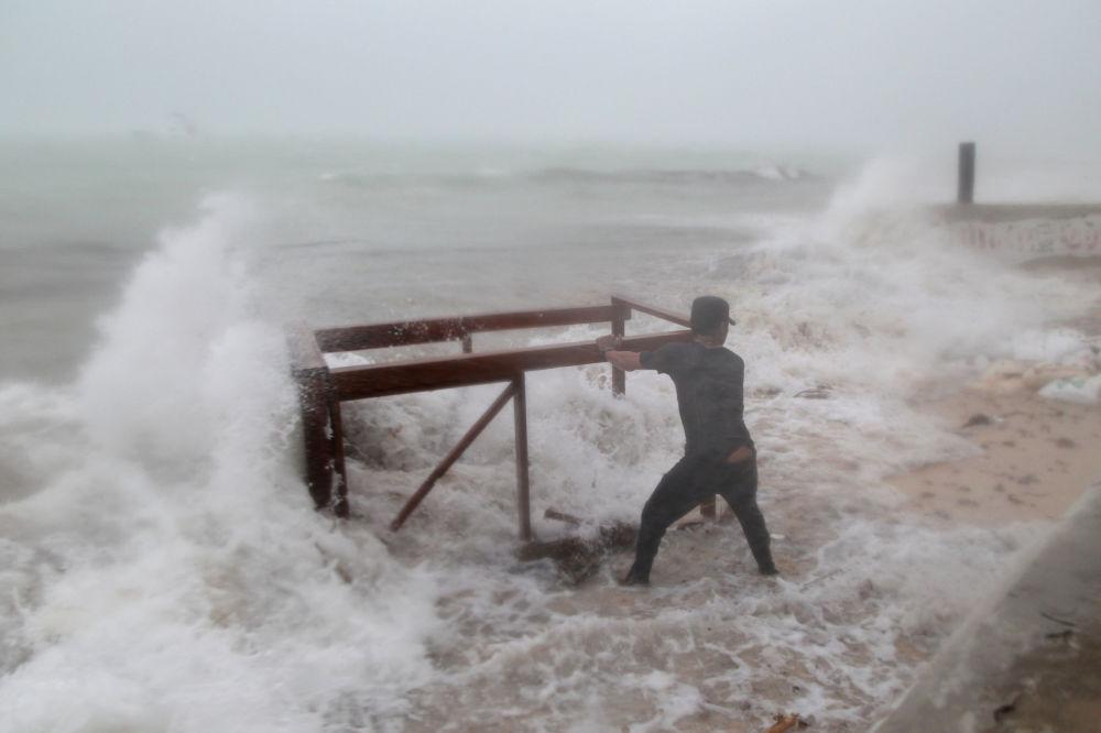 Homem tenta retirar mesa levada ao mar durante o furacão Maria
