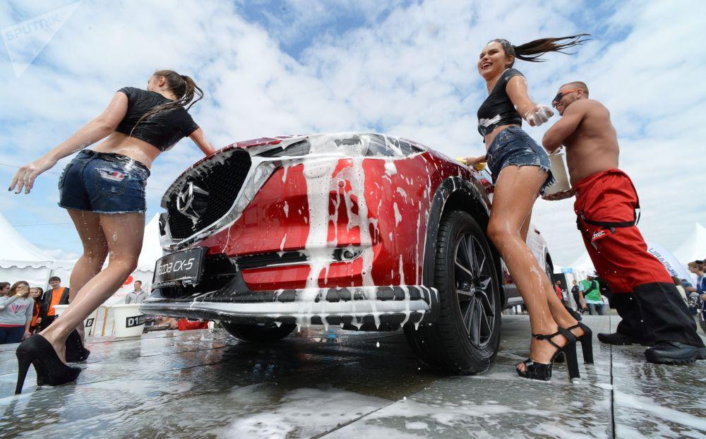 Modelos lavam carros no Salão Automóvel Internacional de Vladivostok