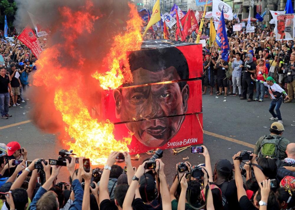 Manifestantes queimam retrato do presidente filipino, Rodrigo Duterte, em Manila