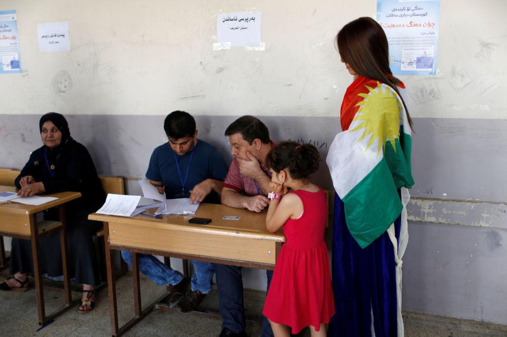 Uma mulher votando durante o referendo curdo em Erbil, Iraque