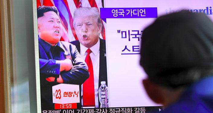 Um homem a ver programa de notícias que mostra Donald Trump e Kim Jong-Un na estação ferroviária em Seul em 9 de agosto de 2017