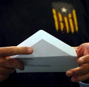 Homem usa uma camiseta com uma bandeira Estelada, símbolo da pró-independência catalã, prepara sua cédula nas eleições parlamentares regionais da Catalunha em Barcelona, setembro de 2015 (foto de arquivo)