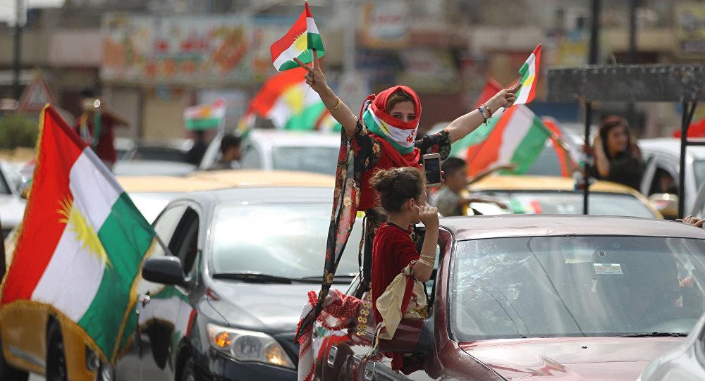 Curda iraquiana com a bandeira mostrando gesto de vitória durante as celebrações em Kirkuk