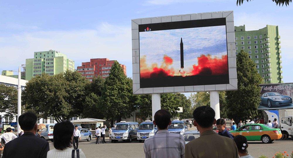 As pessoas a ver o lançamento do míssil balístico Hwasong-12 na televisão da estação ferroviária em Pyongyang, Coreia do Norte, 16 de setembro de 2017