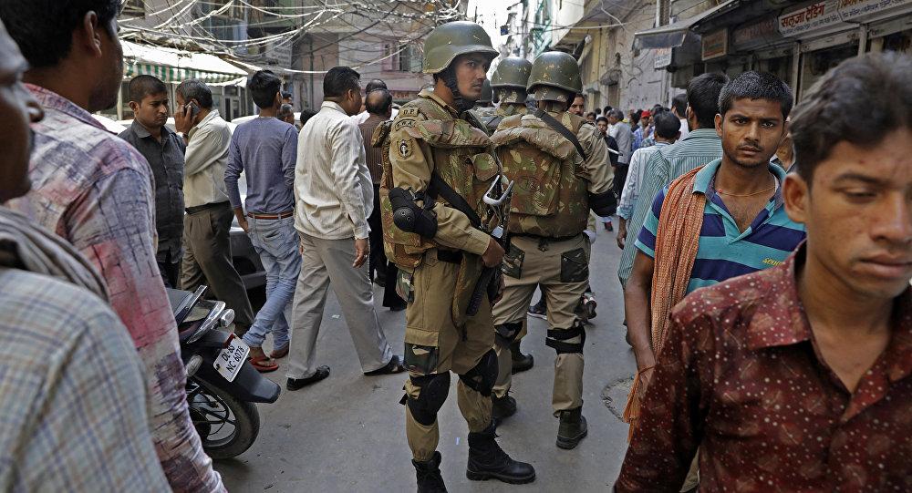 Polícia de Nova Deli cercada por cidadãos em uma rua da cidade, Índia