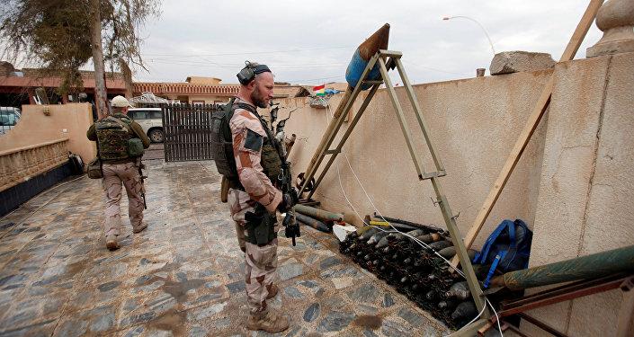 Soldado norte-americano ao olhar para as armas e amunições do Daesh em Mossul, Iraque