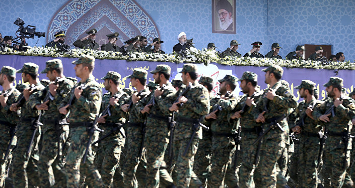 Iran's President Hassan Rouhani, top center, reviews army troops marching during the 37th anniversary of Iraq's 1980 invasion of Iran, in front of the shrine of the late revolutionary founder, Ayatollah Khomeini, just outside Tehran, Iran, Friday, Sept. 22, 2017