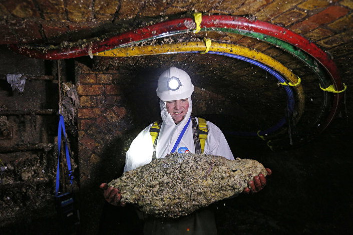 Funcionário com um fatberg durante inspeção nos esgotos de Londres