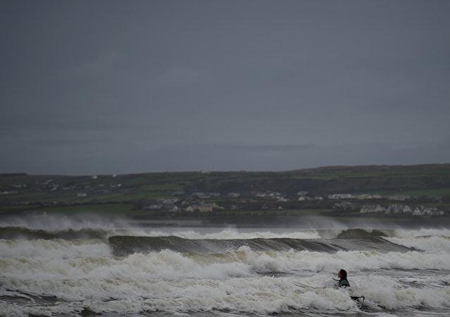 Surfista nada no oceano Atlântico na véspera da chegada do furacão Ophelia, Irlanda, 15 de outubro de 2017