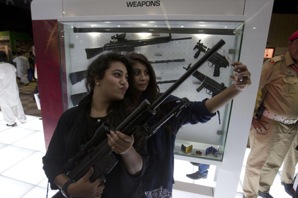 Garotas tiram selfie durante exposição militar no Paquistão, novembro de 2016