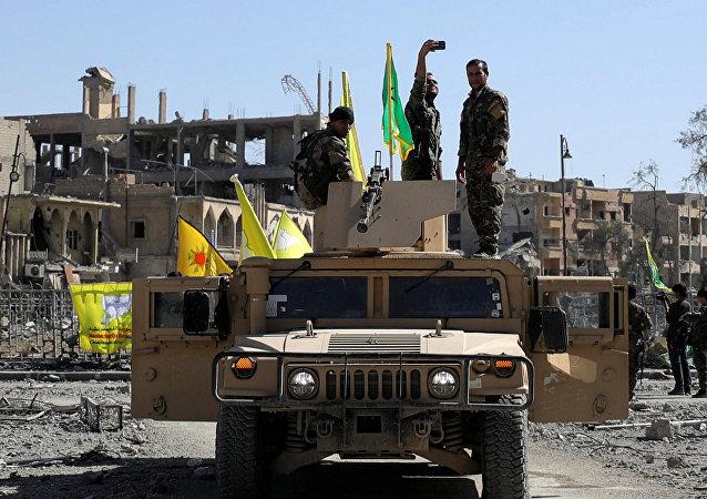 Militante das Forças Democráticas da Síria tira selfie sobre veículo militar em Raqqa