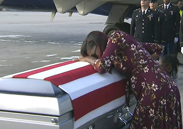 In this Tuesday, Oct. 17, 2017, frame from video, Myeshia Johnson cries over the casket of her husband, Sgt. La David Johnson, who was killed in an ambush in Niger, upon his body's arrival in Miami