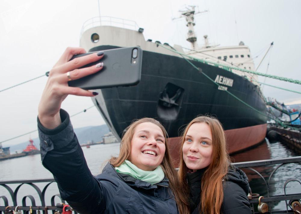 Meninas tiram selfie com quebra-gelo russo Lenin no pano de fundo