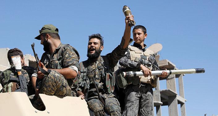 Combatentes das Forças Democráticas da Síria em um veículo armado depois da libertação de Raqqa, Síria, outubro de 2017