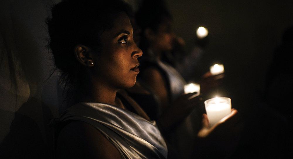 Mulher com vela durante a Cerimônia do Fogo Eterno em Lyon, França, em 2014, no 20º aniversário do genocídio de 2014 em Ruanda