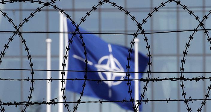 A bandeira da OTAN vista através de cerca farpada em frente à nova sede da OTAN em Bruxelas, maio de 2017