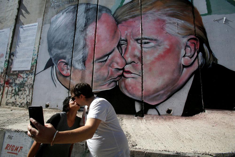 Turistas se beijam perto do grafite retratando um beijo entre o presidente dos EUA, Donald Trump, e o premiê israelense, Benjamin Netanyahu, na Cisjordânia